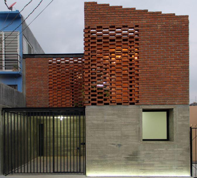 Fachada de casa de dos pisos de ladrillo y hormigón