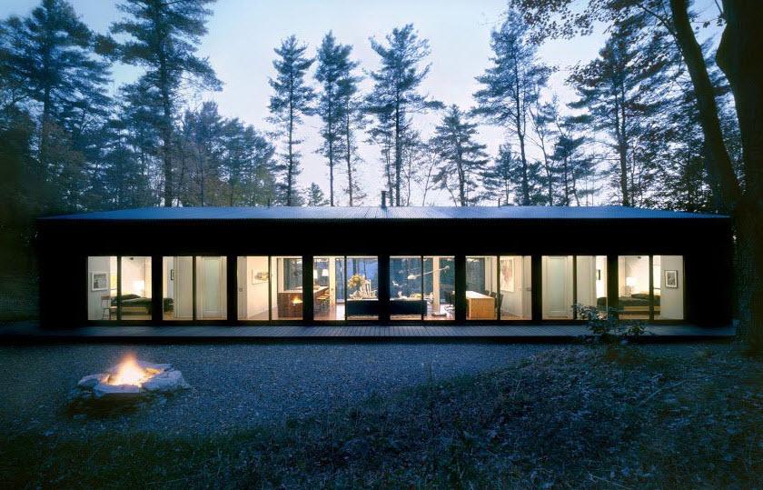 Casa de campo de un piso iluminada al anochecer